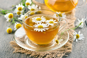 Herbal chamomile tea in glass cup on wooden table